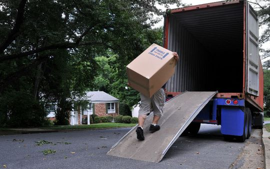 A driver picking up a box to go to storage